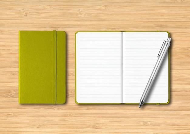 Caderno com forro verde oliva fechado e aberto com uma caneta. maquete isolada em fundo de madeira