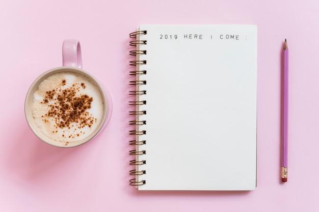 Caderno com inscrição perto de lápis e copo de bebida