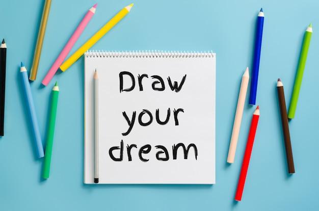Caderno com inspiração desenhe o seu sonho e conjunto de lápis coloridos.