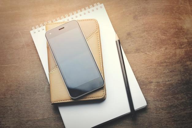 Caderno com lápis e smartphone em fundo de madeira