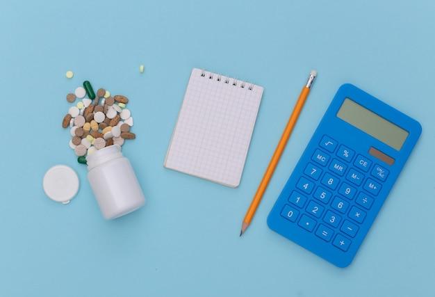 Caderno com lápis, frasco de comprimidos, calculadora em fundo azul pastel. vista do topo