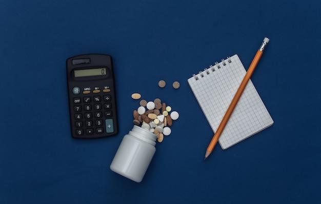 Caderno com lápis, frasco de comprimidos e calculadora em fundo azul clássico. cor 2020. vista superior