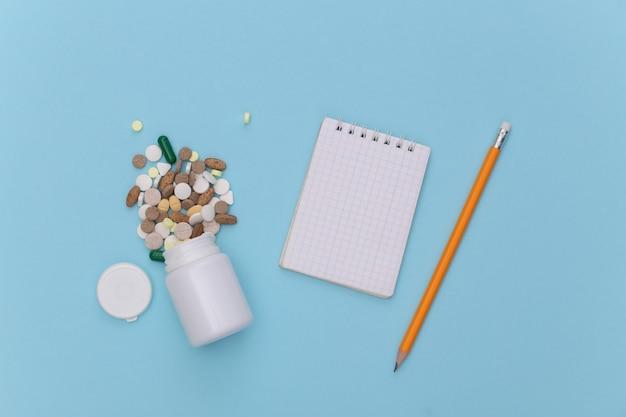 Caderno com lápis, frasco de comprimidos em fundo azul pastel. vista do topo