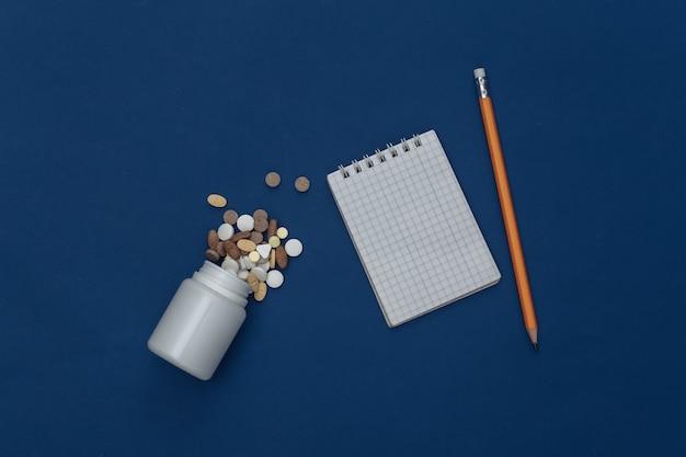 Caderno com lápis, frasco de comprimidos no fundo azul clássico. cor 2020. vista superior
