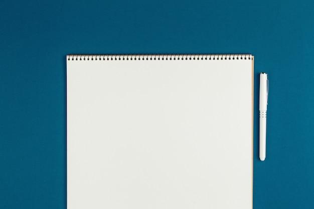 Caderno com lápis na vista superior da parede azul, estudante fazendo lição de casa, mesa de trabalho de escritório plana leigos. bloco de notas vazio na mesa