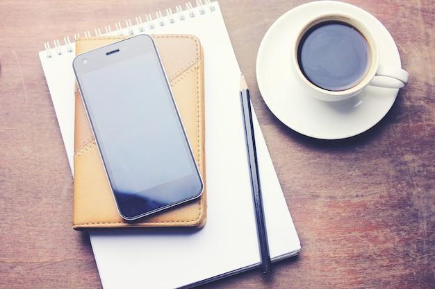 Caderno com lápis, smartphone e xícara de café em fundo de madeira
