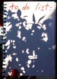 Caderno com lista de tarefas com sombra de planta turva. copie o espaço.