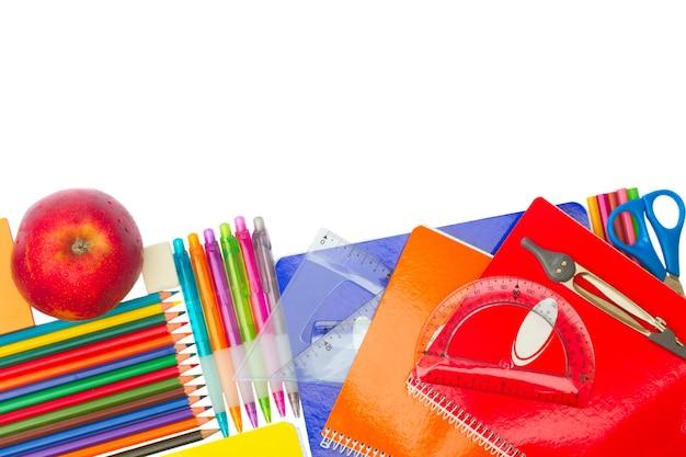 Caderno com material escolar e borda de maçã isolada