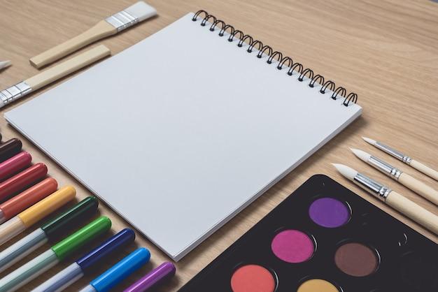 Caderno com muitas canetas coloridas, pincel e paleta de aquarela em madeira marrom