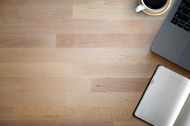 Caderno com o computador do teclado na mesa de madeira do espaço de trabalho e no espaço da cópia.