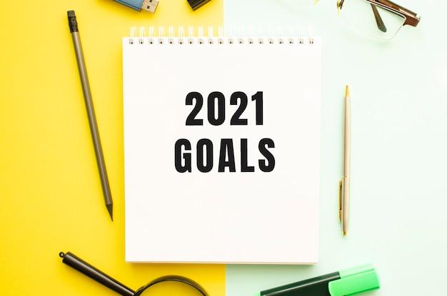 Caderno com o texto 2021 objetivos na mesa do escritório com material de escritório. conceito de fundo de cor amarela. conceito de negócios.
