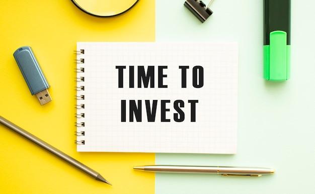 Caderno com o texto, hora de investir na mesa de escritório com material de escritório. conceito de superfície de cor amarela.