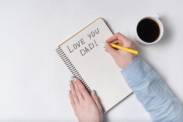 Caderno com o texto te amo pai. mãos femininas escrevendo no notebook. café da manhã.
