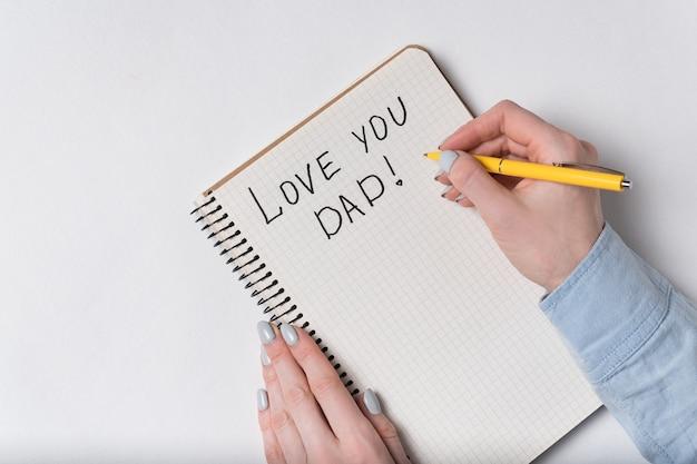 Caderno com o texto te amo pai. vista superior das mãos femininas, escrevendo no notebook em fundo branco.