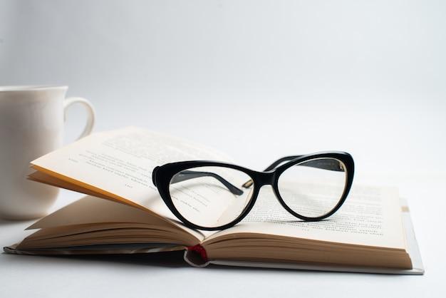 Caderno com óculos e caneta, livro com óculos, caderno azul com óculos, livro com xícara de chá
