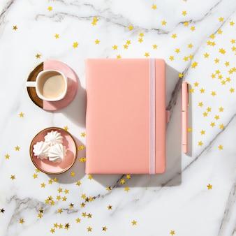Caderno com páginas vazias para texto, caneta, xícara de café, caixas de presente, brilhos de ouro na mesa branca