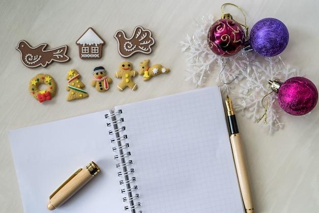 Caderno com pão de mel e caneta na mesa de madeira