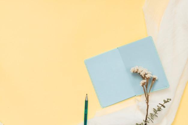 Caderno com ramo de flores e caneta