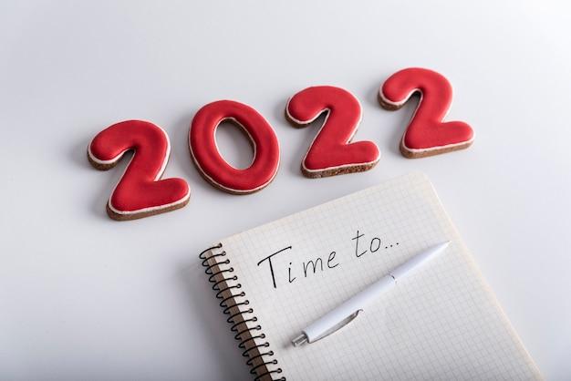 Caderno com tempo para a inscrição e números vermelhos 2022 em fundo branco. metas e planos de sonhos para 2022.