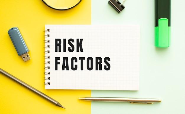Caderno com texto fatores de risco na mesa de escritório com material de escritório. conceito de fundo de cor amarela. conceito de negócios.