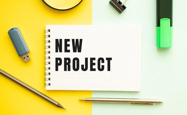 Caderno com texto novo projeto na mesa de escritório com material de escritório. conceito de fundo de cor amarela. conceito de negócios.