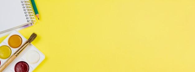 Caderno com tintas em um fundo amarelo.