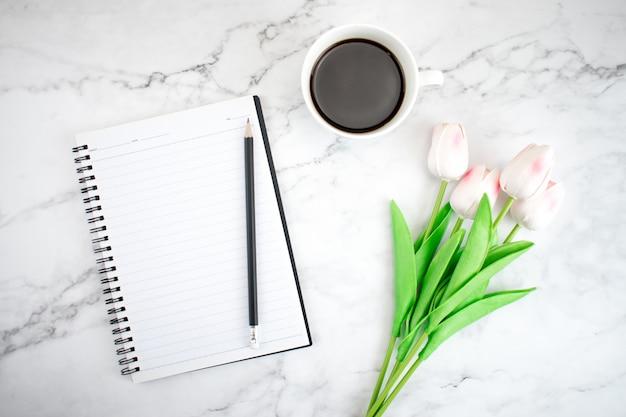 Caderno com tulipas na mesa de mármore