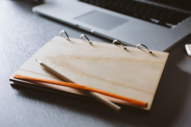 Caderno com uma tampa de madeira e um lápis e um laptop em uma mesa de madeira cinza