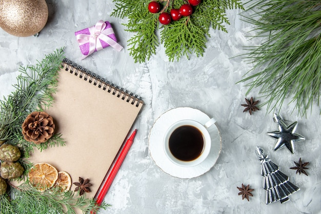 Caderno com vista de cima, fatias de limão secas, ervilhas, ramos de pinheiro, chávena de chá vermelho na superfície cinzenta