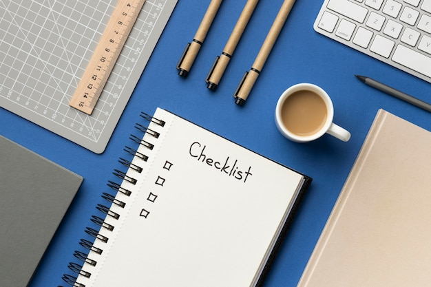 Caderno com vista superior com lista de verificação na mesa