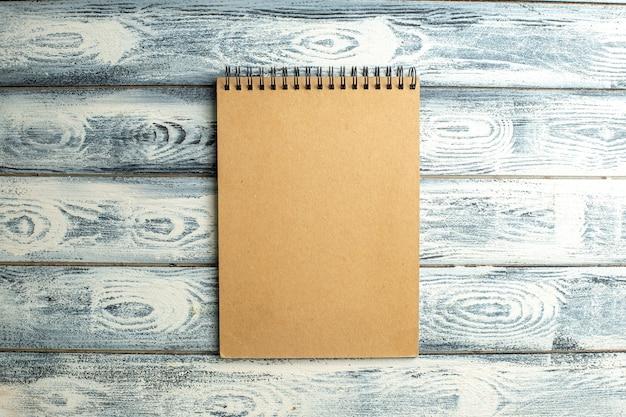 Caderno com vista superior em fundo de madeira