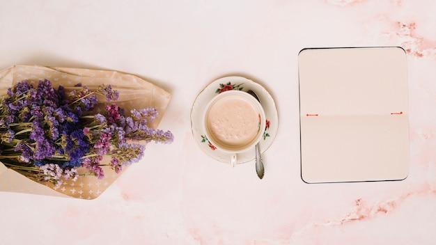 Caderno com xícara de café e buquê de flores na mesa
