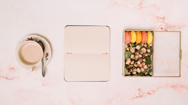 Caderno com xícara de café e caixa com flores na mesa
