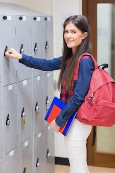Caderno de abertura de estudante sorridente na universidade
