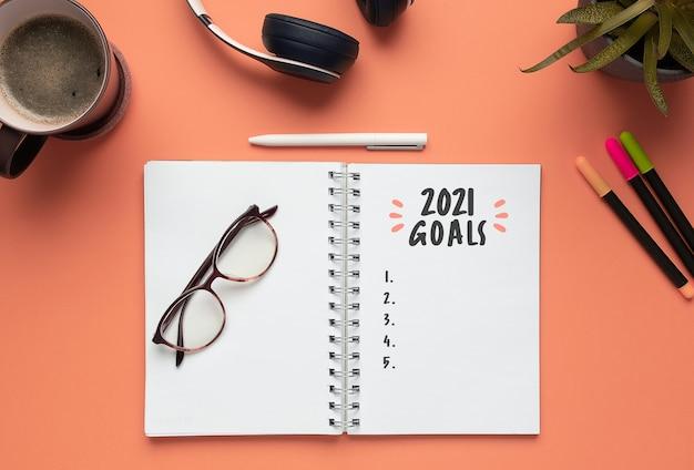 Caderno de ano novo de 2021 com lista de metas em uma rosa