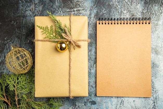Caderno de bola de natal de ramos de pinheiro de presente de natal de vista superior na superfície cinza
