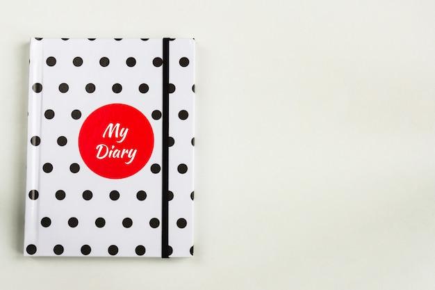 Caderno de bolinhas preto e branco com círculo vermelho e minha inscrição de diário na capa.