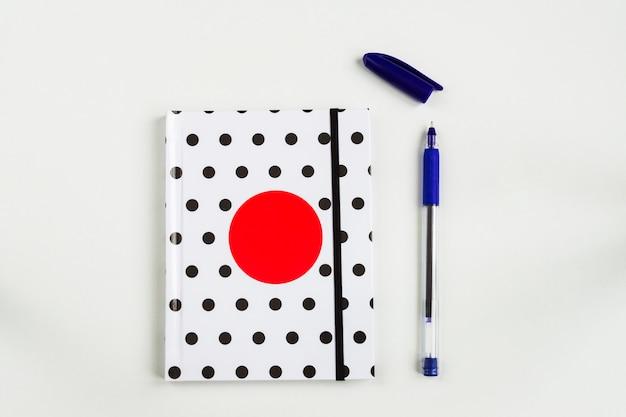 Caderno de bolinhas preto e branco com círculo vermelho na capa e caneta azul na mesa branca. vista superior, configuração plana mínima