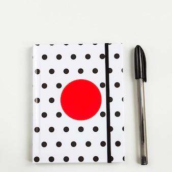 Caderno de bolinhas preto e branco com um círculo vermelho na capa e caneta preta na mesa branca. vista superior, configuração plana mínima