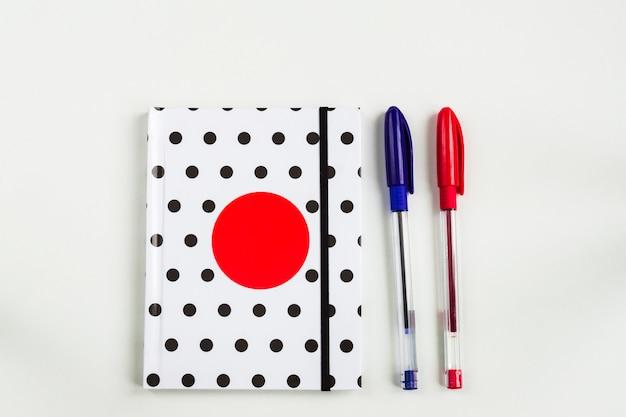 Caderno de bolinhas preto e branco com um círculo vermelho na capa e canetas azuis e vermelhas na mesa branca. vista superior, configuração plana mínima