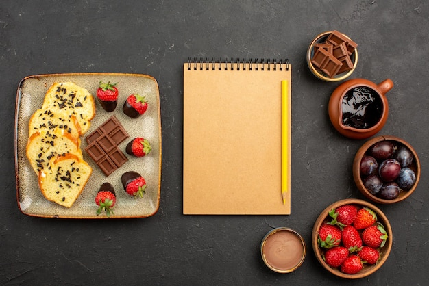 Caderno de bolo e morangos com vista de cima e lápis entre os pedaços de bolo com chocolate à esquerda e tigelas com morangos e frutas vermelhas e calda de chocolate no lado direito da mesa