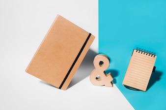 Caderno de capa marrom; sinal de madeira e comercial e bloco de notas em espiral no fundo branco e azul