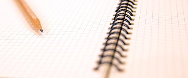 Caderno de close-up com um lápis em cima da mesa.