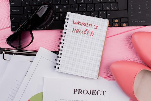 Caderno de coisas femininas na área de trabalho do escritório
