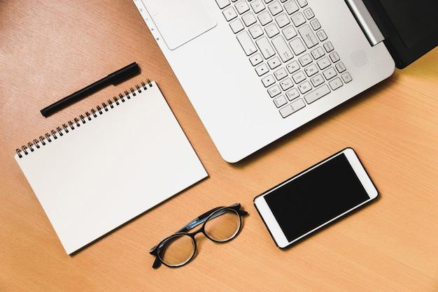 Caderno de computador de negócios lwith smartphone e notebook na mesa de madeira