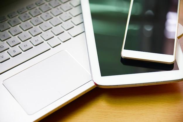 Caderno de computador portátil com telefone smarth e taplet na mesa de madeira no escritório de negócios