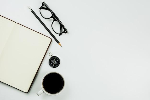 Caderno de couro de brown e um copo de café no fundo branco da mesa com espaço da cópia.