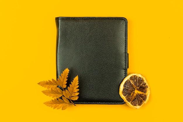 Caderno de couro preto com conceito de negócio de maquete de flores secas, vista superior e foto de fundo amarelo
