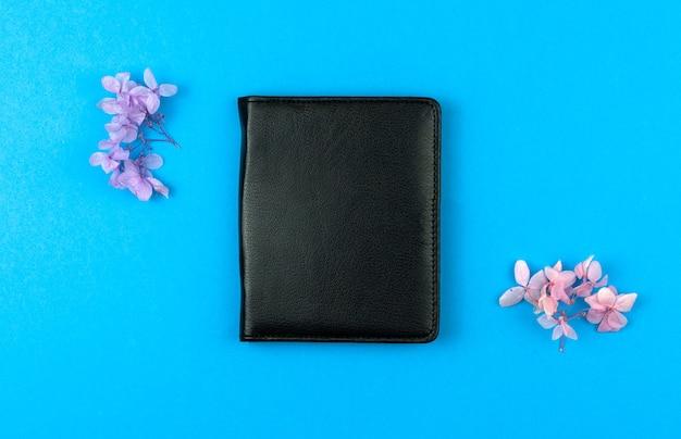 Caderno de couro preto com flores secas em um fundo azul da área de trabalho, configuração plana e foto de vista superior