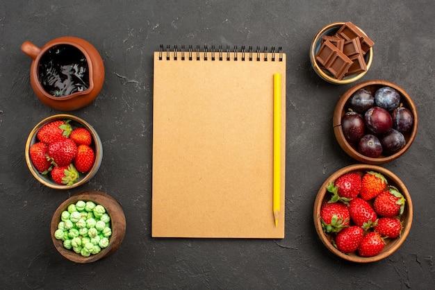 Caderno de creme e lápis de frutas e doces de cima entre morangos com molho de chocolate, chocolate verde, doces e frutas vermelhas em tigelas marrons sobre a mesa